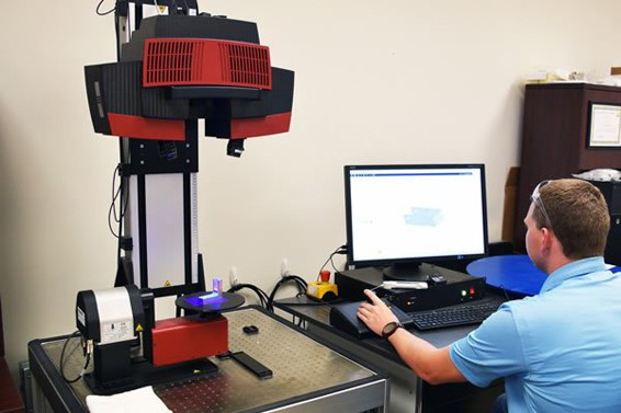 Engineer sitting at a computer next to a 3D scanning machine used to inspect vehicle parts