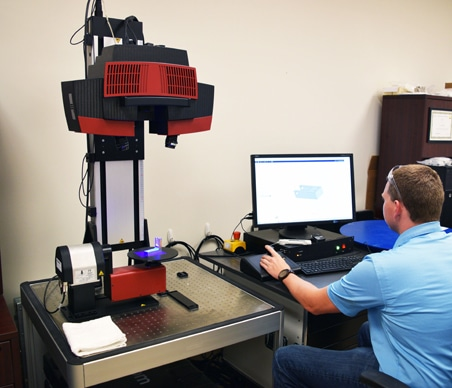 Man sitting at a computer operating a 3D scanning machine