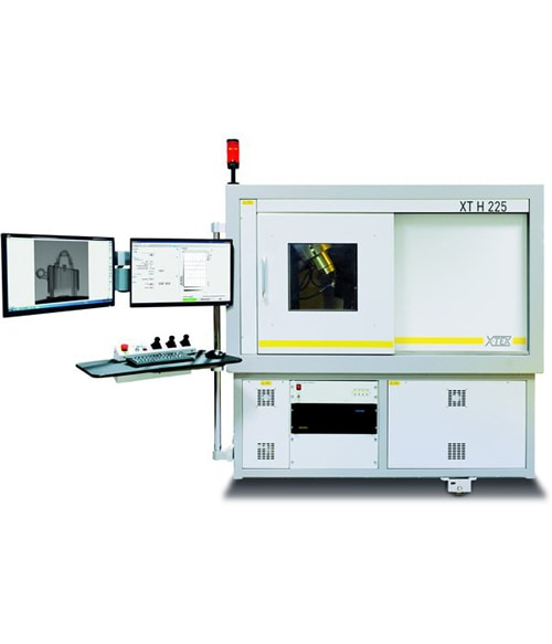 X-ray scanning machine connected to a computer with duel monitors used for non-destructive X-ray inspections on automotive parts.