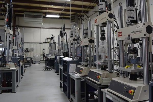 View inside an automotive testing lab with heavy machinery used for compression and fatigue testing on automotive parts