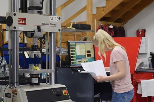 Blonde female engineer holding papers and monitoring a mechanical testing machine and computer screen