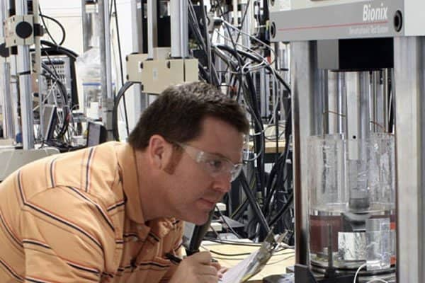 Male engineer wearing safety glasses and writing on clipboard while observing a mechanical testing machine
