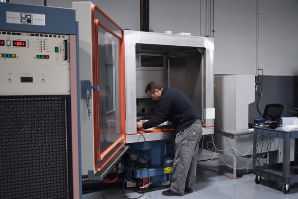 Engineer with safety gear standing in front of large square vibration testing machine