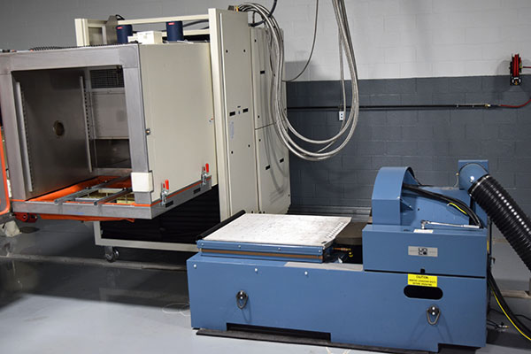 Three axis electrodynamic vibration shaker and a thermal chamber which can be slide above the shaker table to perform thermal vibration testing.