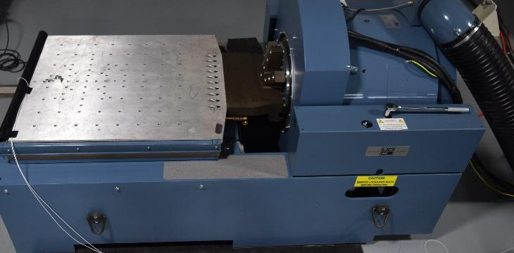 Small blue machine called an Electrodynamic Shaker. This is a piece of vibration testing equipment used to emulate real world conditions based upon the signal sent from the vibration controller