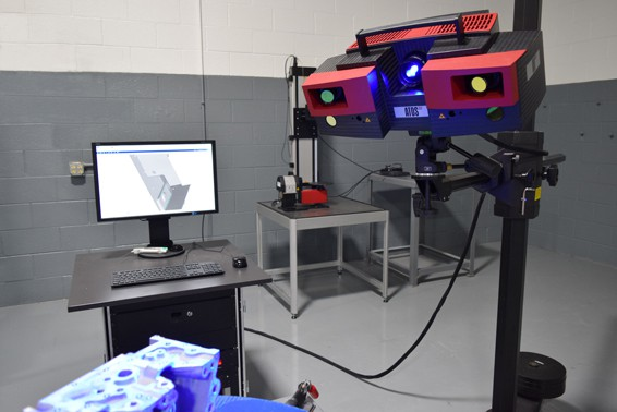 A 3D Scanning machine is projecting a blue light onto an object, and showing the model on a computer screen.